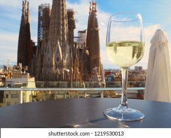 BARCELONA, SPAIN – November 01, 2018: La Sagrada Familia, the cathedral designed by architect Gaudi, in the background with a class of white wine in the front.