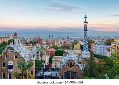 Barcelona, Spain - November 02, 2018:  View of Barcelona from Park Guell at the sunset. In the foreground the colourful buildings of the main entrance. Barcelona, Spain.