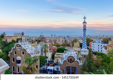 Barcelona, Spain - November 03, 2018:  View of Barcelona from Park Guell at the sunset. In the foreground the colourful buildings of the main entrance. Barcelona, Spain.