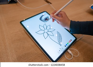 Barcelona, Spain - November 07, 2018: Woman holding a new iPad Pro at Apple Store. She is drawing with apple pencil
