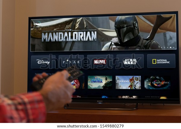 Barcelona, Spain. November 2019: Man holds a remote control With the new Disney plus screen on TV, showing The Mandalorian space western television series. .Illustrative editorial. Disney plus is an