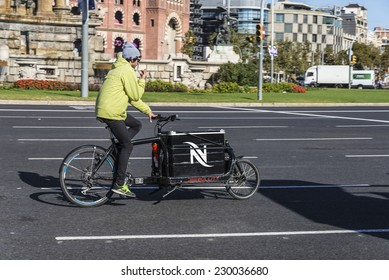 Barcelona, Spain - November 7, 2014: An interesting bike with a cargo box running through a square in Barcelona