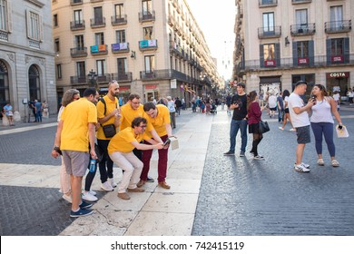 Barcelona, Spain, Oct. 13, 2017: Young employees on a company scavenger hunt, competing against other teams, wearing matching shirts, getting clues, meeting in Plaza Jaume in the Gothic Quarter.