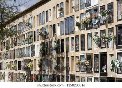 Barcelona, Spain - October 10, 2017: Multi-storey columbarium with bright artificial and natural flowers in the Windows of funeral urn (urns with ashes). Saving expensive urban areas