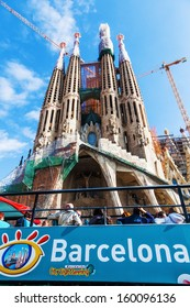 BARCELONA, SPAIN - OCTOBER 12: Basilica Sagrada Familia with a tourist bus and uniedetified people on October 12, 2013 in Barcelona. Designed by Antoni Gaudi it will be completed circa 2026.