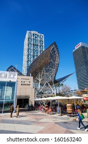 BARCELONA, SPAIN - OCTOBER 13: highrises and a whale sculpture with unidentified people on October 13, 2013 in Barcelona. The sculpture was designed by world reknown architect Frank O. Gehry.
