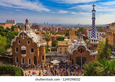 Barcelona, Spain - October 21, 2013: Two buildings at the entrance of the famous Antoni Gaudi Park Guell with the view of the city skyline in the background