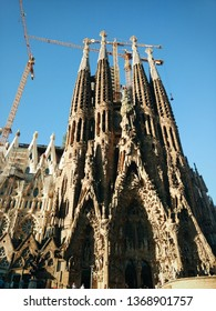 Barcelona, Spain - October 22nd, 2018: Main facade from La Sagrada Familia, gothic church still unfinished designed by the architect Antoni Gaudí. Crane in the background in church building.