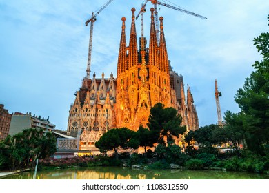 BARCELONA, SPAIN - OCTOBER 24, 2015: Illuminated Sagrada Familia Cathedral behind the trees at night. Designed by Antoni Gaudi in Gothic style is under construction. Reflection in the water