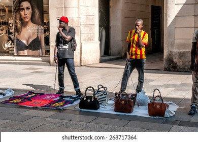 Barcelona, Spain - October 2nd, 2014: Illegal street vendors with brand copies, ready to run away