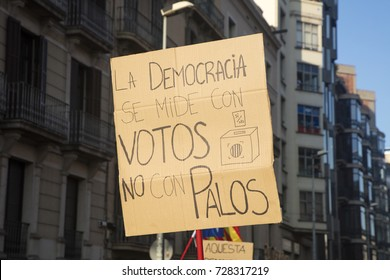 """Barcelona, Spain - October 3, 2017. Demonstrators bearing placards during protests for independence in Barcelona. On that banner is said: """"Democracy is measured with votes, not with violence"""""""