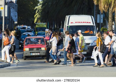 BARCELONA, SPAIN - OCTOBER 6, 2014: A group of people cross one of the crosswalks of the city.