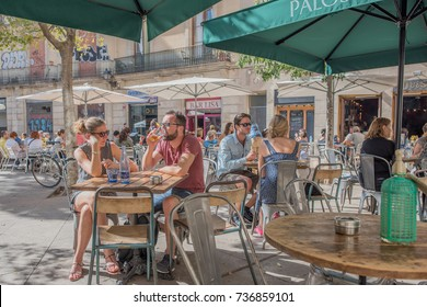 Barcelona, Spain, October 9, 2017: A young couple enjoys lunch in the George Orwell Plaza, a popular gathering spot in the Gothic Quarter  neighborhood, known for its ancient buildings and streets.