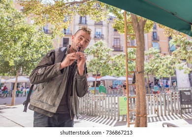 Barcelona, Spain, October 9, 2017: A street performer plays the recorder for people in George Orwell Square, a famous plaza in Barcelona's Gothic Quarter, known for its connection to the author.