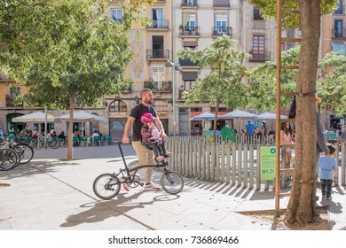 Barcelona, Spain, October 9, 2017: A father helps his young daughter ride a bicycle through the famous George Orwell Square in the Gothic Quarter. The plaza is known for its connection to the author.