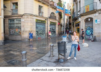Barcelona, Spain, October 9, 2017: A young woman waits for the bus in the famous George Orwell Square in Barcelona's Gothic Quarter. The neighborhood is known for its ancient buildings and streets.
