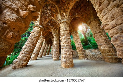 Barcelona, Spain. Park Guell. Stone pillars with archs at sunset among green trees and plants. Famous touristic destination landmark for walking tours.