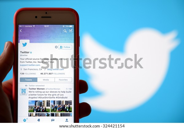 BARCELONA, SPAIN - SEP 30, 2015: Hand holding a mobile phone and using the social network Twitter application.