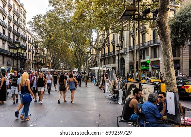 BARCELONA, SPAIN - SEPTEMBER 10, 2016: Few Tourists walk on the famous Las Ramblas. La Rambla Boulevard is one of the most recognized streets in the world.