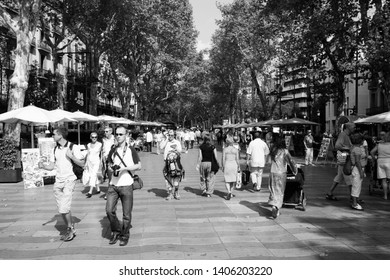 BARCELONA, SPAIN - SEPTEMBER 13, 2009: Tourists visit Ramblas avenue in Barcelona, Spain. Rambla boulevard is one of the most recognized streets in the world.