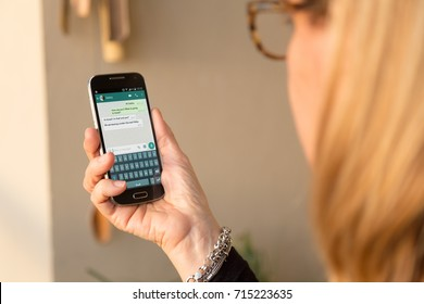 BARCELONA, SPAIN - SEPTEMBER 13, 2017: Senior woman with smartphone in her hands and a whatsapp conversation on the screen. Grandmother chatting. Technology. Communications.