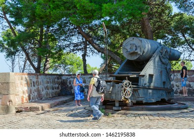 BARCELONA, SPAIN - SEPTEMBER 13, 2018: Unknown tourists are near cannon (coast howitzer of late 19th century) at Montjuic Fortress, Barcelona, Spain