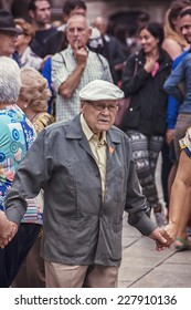 BARCELONA, SPAIN - SEPTEMBER 15, 2013: Close view of people (seniors) holding hands and dancing Sardana at Plaza Nova. The dance is a type of circle dance typical of Catalonia.