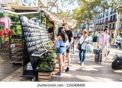 Barcelona, Spain - September 20, 2017: Tourists taking their luggage along Les Rambles while a young couple chooses a gift in Barcelona, Catalonia, Spain