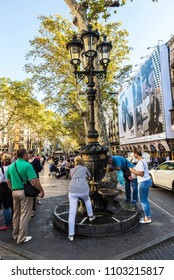 Barcelona, Spain - September 20, 2017: Font de Canaletes, ornate fountain crowned by a lamp post, with people around in Les Rambles of Barcelona, Catalonia, Spain