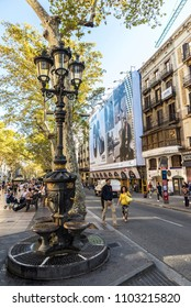 Barcelona, Spain - September 20, 2017: Font de Canaletes, ornate fountain crowned by a lamp post, with people walking around in Les Rambles of Barcelona, Catalonia, Spain