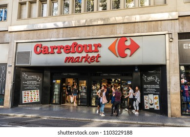 Barcelona, Spain - September 20, 2017: Young tourists in front of a Carrefour market in Les Rambles of Barcelona, Catalonia, Spain