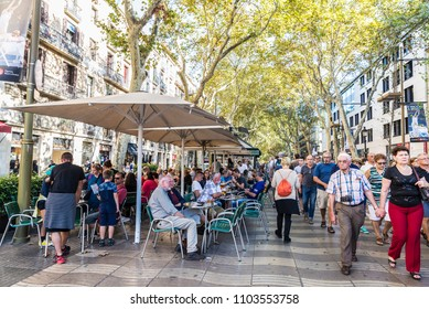Barcelona, Spain - September 20, 2017: Terrace of a bar and people walking along Les Rambles in Barcelona, Catalonia, Spain