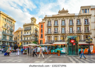 Barcelona, Spain - September 26 2018: Pedestrians walk the colorful street La Rambla past buses and shops in Barcelona Spain