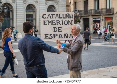 BARCELONA, SPAIN - SEPTEMBER 27, 2017: Portuguese radio station RSF journalist interviews a protester in the plaza in front of Barcelona City Hall.