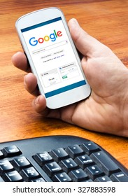 BARCELONA, SPAIN - SEPTEMBER 4,2015: Male hand holding on smartphone with Google Web Search homepage on the screen (new Google logo)