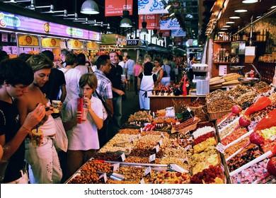 BARCELONA, SPAIN - SEPTEMBER 9, 2009: Tourists visit famous La Boqueria market in Barcelona. One of the oldest markets in Europe that still exist. Established 1217.