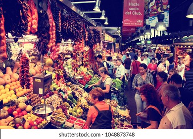 BARCELONA, SPAIN - SEPTEMBER 9, 2009: Tourists visit famous La Boqueria market in Barcelona. One of the oldest markets in Europe that still exist.