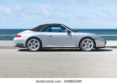 BARCELONA, SPAIN-APRIL 12, 2021: 2005 Porsche 911 (997) Carrera 4S Cabriolet (side view) parked by the sea