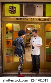 Barcelona, Spain-May 28, 2013: Barber talking to a woman on the steps in front of mens barber shop in Barcelona, Spain