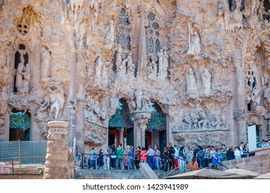 Barcelona,Catalonia,Spain. May 8,2017 : Exterior with beautiful sculpture of famous unfinished Roman Catholic church Sagrada Familia. Group of tourists queuing at the entrance of Nativity Facade.