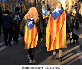 Barcelona/Spain, 2019-02-16. Two women with the catalan secessionist flag walk in a demonstration to demand the freedom of secessionist politicians who violated the Spanish Constitution