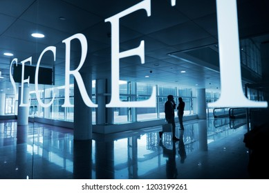 Barcelona-Spain- Circa May 2018. People calling by phone in the Barcelona's airport lobby with a Secret text label over. Confidential concept image.