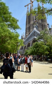 Barcelona/Spain - June 03 2019: Tourist taking photo with smartphone of a family who are standing in front of the famous cathedral La Sagrada Familia in Barcelona, Spain