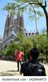 Barcelona/Spain - June 03 2019: Young man taking photo with smartphone of tourist standing in front of the famous cathedral La Sagrada Familia in Barcelona