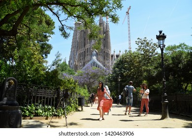 Barcelona/Spain - June 3 2019: Young woman in front of camera, surrounded by other tourists in the public park, with the famous Cathedral La Sagrada Familia in the background