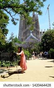 Barcelona/Spain - June 3 2019: Young woman fixing the settings on her camera, in order to get ready to take photos of the famous cathedral La Sagrada Familia in Barcelona on a sunny day