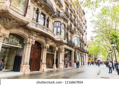 BARCELONA,SPAIN-April 13,2018: Many people walking around La rambla shopping street.This area has many brand name stores throughout the street.