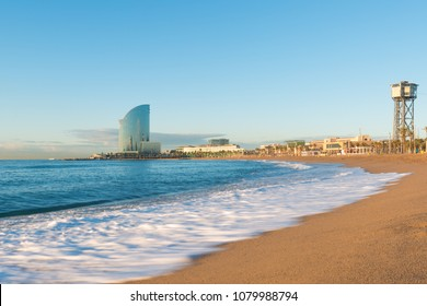 Barceloneta Beach in Barcelona with colorful sky at sunrise. Seafront, beach,coast in Spain. Suburb of Barcelona, Catalonia