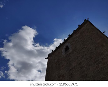 Barcelos medieval tower against blue cloudy sky.