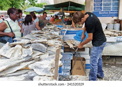 Barcelos, Portugal - August 23, 2012: A man is cutting bacalhau during the market day. Bacalhau dishes are very common in Portugal.